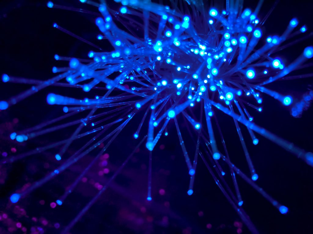 collection of light blue fibre optic cables on a dark blue background