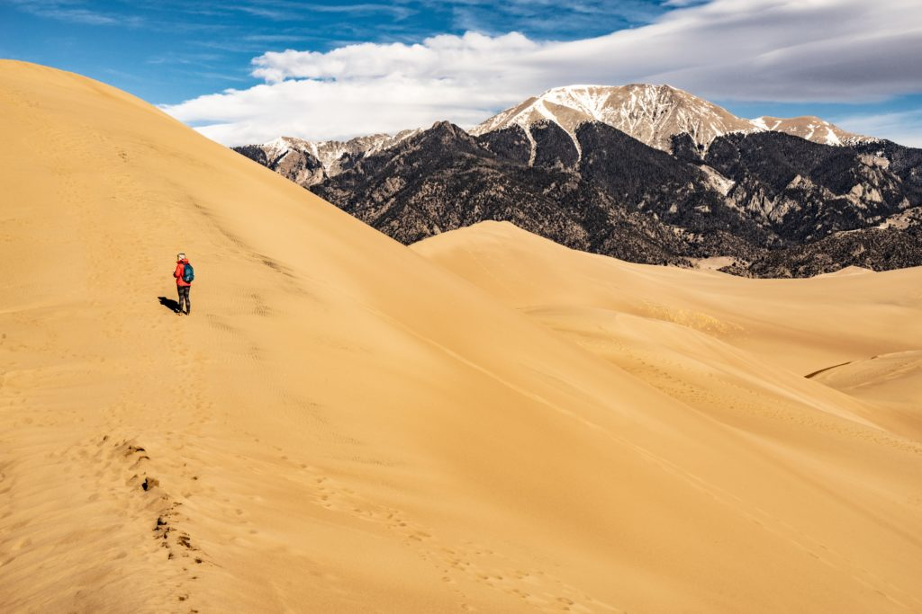 person on sand dune with mountains in the background